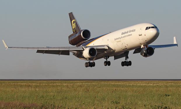 Lądowanie McDonnella Douglasa UPS o poranku widziane z zamkniętej drogi kołowania samolotów.