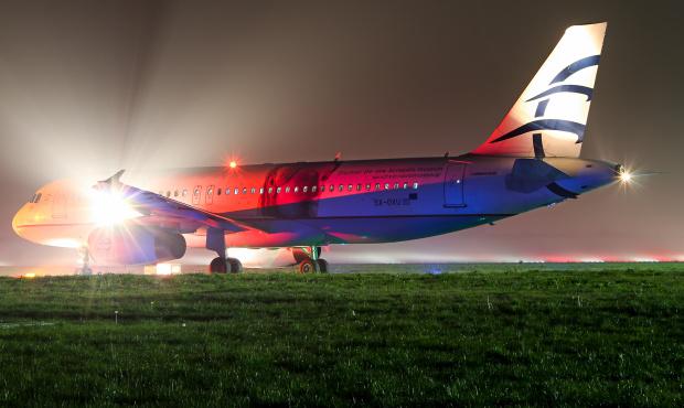 Szykujący się do startu airbus greckiej linii Aegean w jesiennej mgle.